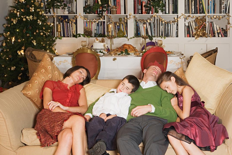 Family sleeping on sofa at Christmas